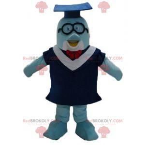Mascota del delfín azul con bata y gorra de estudiante. -