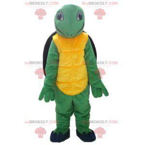Přátelský a usměvavý maskot žlutozelené a černé želvy -