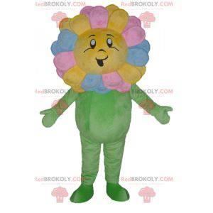 Maskotka ładny gigantyczny i uśmiechnięty wielobarwny kwiat -
