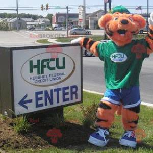 Orange and black tiger mascot in green and blue outfit -