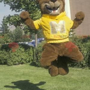 Maskot medvěd hnědý se žlutou mikinou - Redbrokoly.com