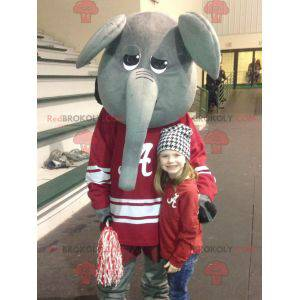 Gray and funny elephant mascot in red sportswear -