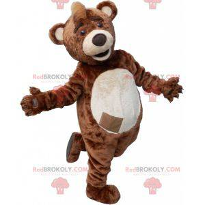 Brown and beige teddy bear mascot with a crest on the head -