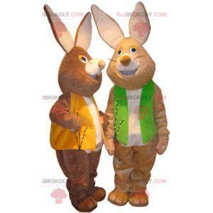 2 maskoti hnědých a bílých králíků s barevnými vestami -