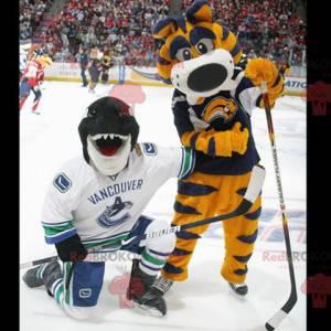 2 maskoti, žlutý a modrý tygr a orca, černý žralok -