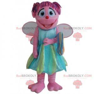 Glimlachende roze fee mascotte met een kleurrijke jurk -