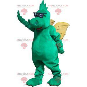 Zielony smok maskotka z żółtymi skrzydłami i okularami -