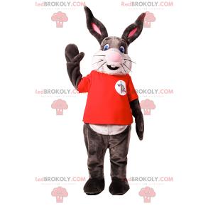Kaninchenmaskottchen mit großem Lächeln und rotem T-Shirt -
