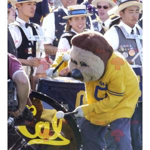 Medvěd hnědý maskot v žluté a modré sportovní oblečení -