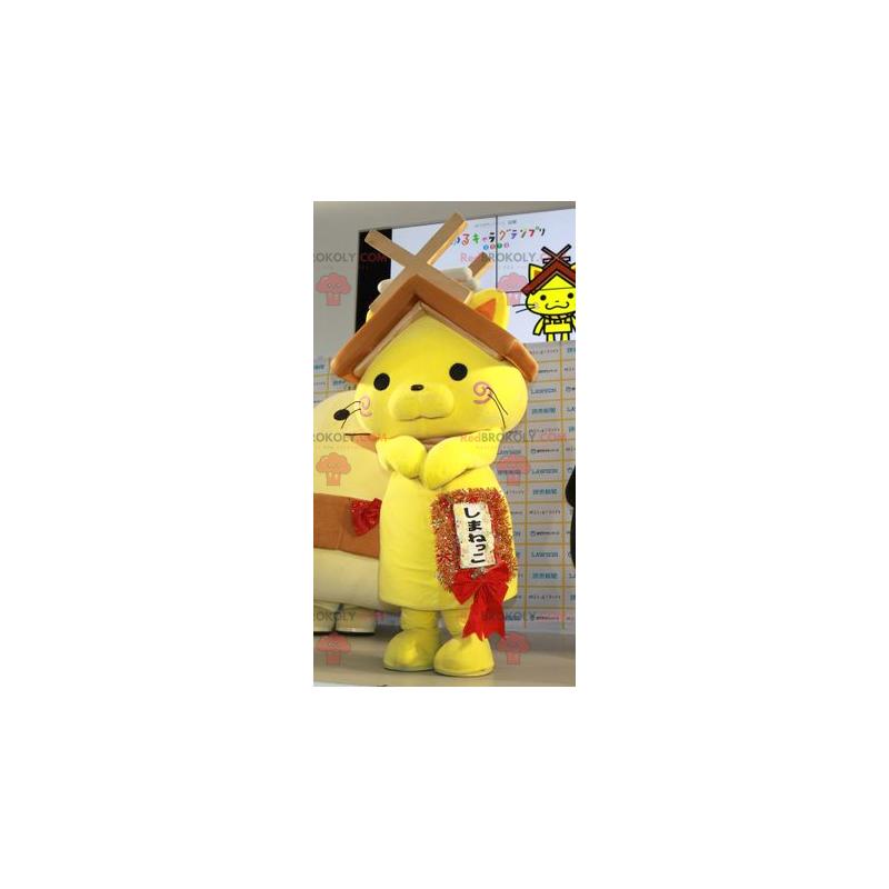 Gelbes Katzenmaskottchen mit einem Hausdach auf dem Kopf -