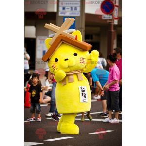 Yellow cat mascot with a house roof on the head - Redbrokoly.com