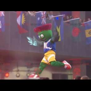 Zelený a červený artyčok maskot v modré a žluté oblečení -