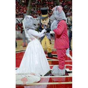 2 maskoti šedých vlků oblečeni v červené a bílé barvě -