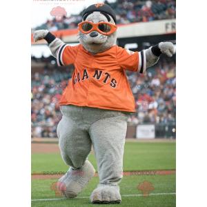 Graues Seelöwenmaskottchen mit einem orangefarbenen T-Shirt -