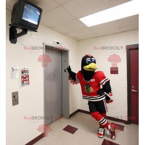 Czarno-biały ptak maskotka z czerwoną odzież sportową -