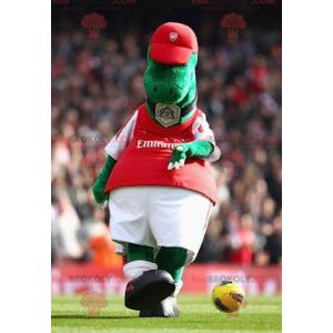 Zielona maskotka dinozaura w czerwono-białej odzieży sportowej
