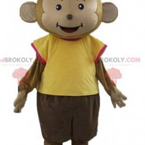 Braunes Affenmaskottchen gekleidet in einem bunten Outfit -