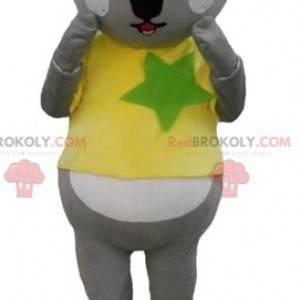 Mascotte koala grigio e bianco con una maglietta gialla e verde