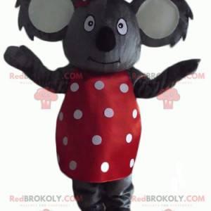 Grå koala maskot med en rød kjole med hvide prikker -