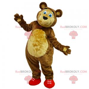 Niedźwiedź maskotka z niebieskimi oczami i czerwonymi trampkami