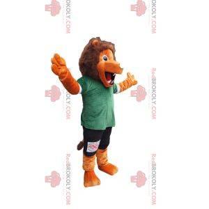 Pomarańczowa maskotka lwa z zielono-czarną odzieżą sportową