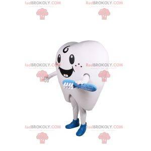 Glimlachende witte tandmascotte en blauwe tandenborstel