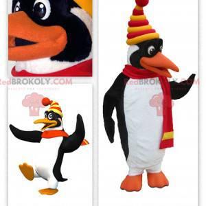 Maskotka ładny biały i czarny pingwin ubrany w zimowe ubrania -