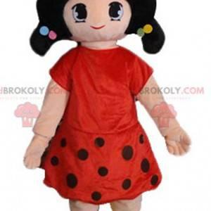 Maskot tmavovláska oblečená v červených šatech s puntíky -