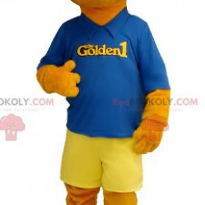 Oranžový pes maskot oblečený v modré a žluté barvě -