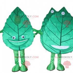 2 maskoter med gigantiske og smilende grønne blader -