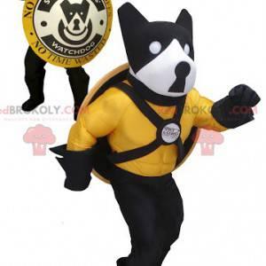 Schwarzes gelbes und weißes Hundemaskottchen mit einem Schild -