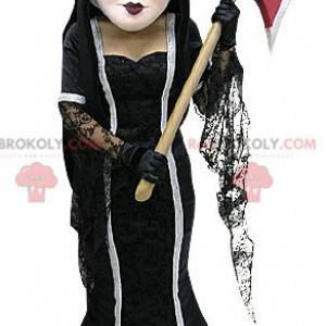 Braunes Hexenmaskottchen im Kleid mit einer Axt - Redbrokoly.com