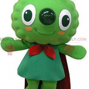 Sehr lächelndes grünes Schneemannmaskottchen mit einem Umhang -