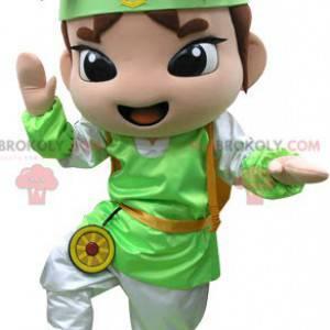 Brązowy chłopiec maskotka z zielono-białym strojem -