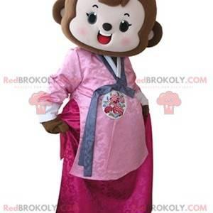 Braunes Affenmaskottchen gekleidet im rosa Kleid -