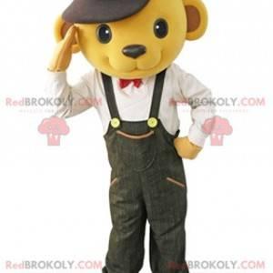 Žlutý medvěd maskot oblečený v montérkách s baret -