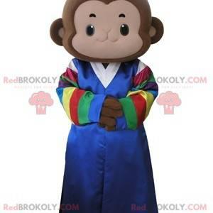 Hnědá opice maskot oblečený v různobarevných šatech -
