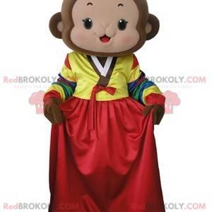 Brun ape maskot med en fargerik kjole - Redbrokoly.com
