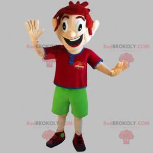 Veldig smilende rødhåret guttemaskot med grønne shorts -