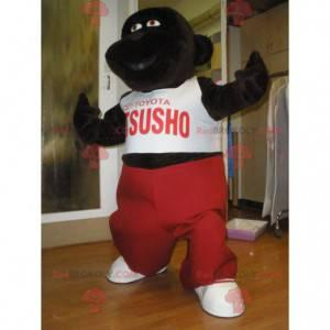 Mascota gorila marrón oscuro con un traje rojo y blanco -
