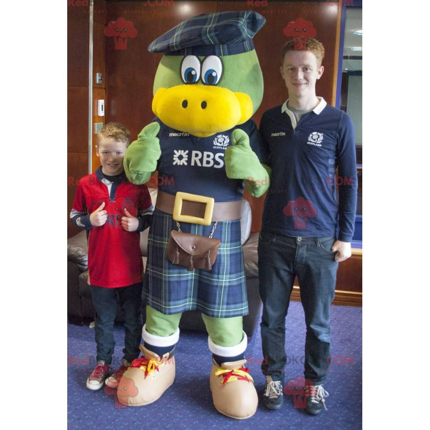 Zelený a žlutý pták maskot oblečený ve skotštině -
