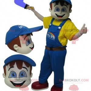 Malarz maskotka ubrany na żółto z niebieskim kombinezonem -