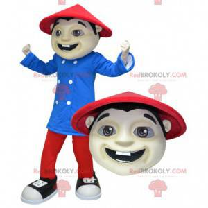 Asiatisches Mannmaskottchen gekleidet in Rot und Blau -