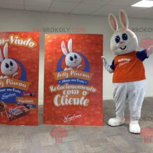 Baculatý a roztomilý maskot bílého králíka oblečený v oranžové