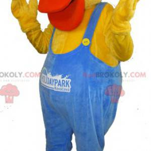 Yellow and orange duck mascot dressed in blue overalls -