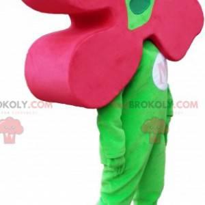 Grünes Schneemannmaskottchen mit einer Blume als Kopf -