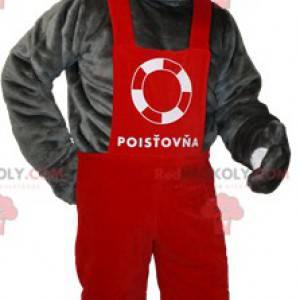 Graues Teddybär-Maskottchen in rotem Overall und Mütze -