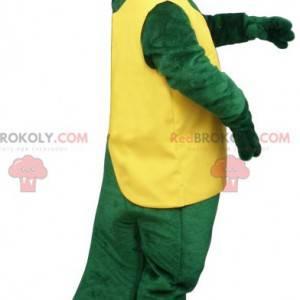 Zelený krokodýl maskot v žluté a červené oblečení -