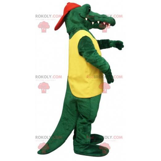 Grünes Krokodilmaskottchen im gelben und roten Outfit -