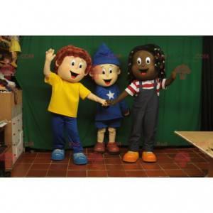 3 fröhlich aussehende Kindermaskottchen mit bunten Outfits -